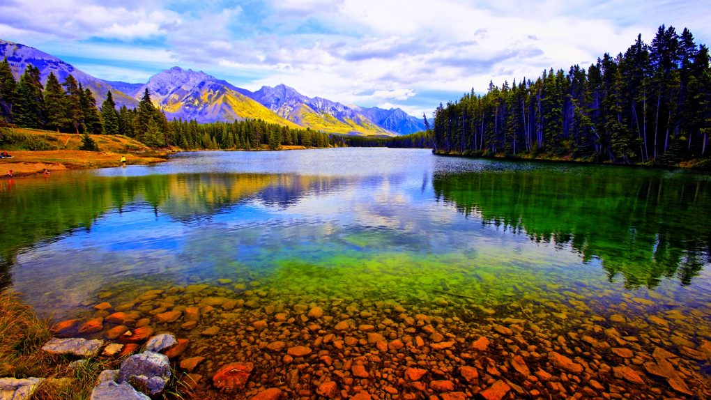 Reflection of mountains and trees in a lake, Lake Johnson, Banff National Park, Alberta, Canada --- Image by © George Oze Photography/SuperStock/Corbis